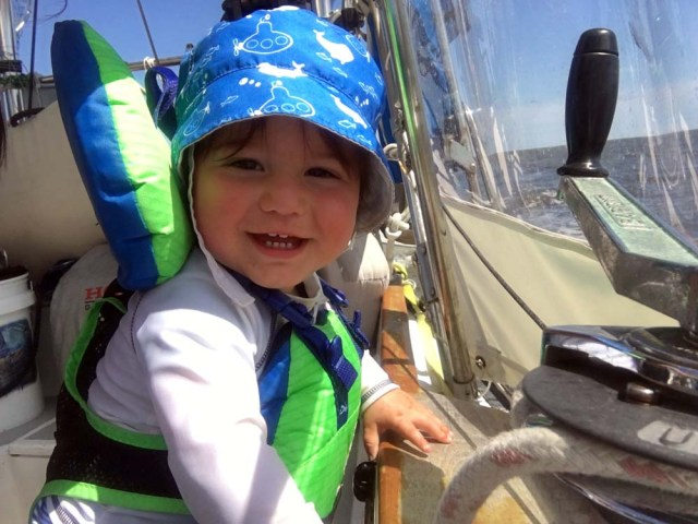 Sailing with a baby in his Salus lifejacket in the cockpit with weathercloths up