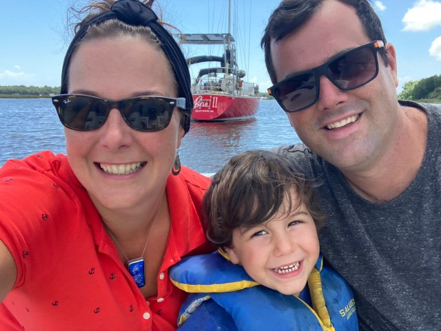 Cruising family with red Sabre 42 sailboat in the background