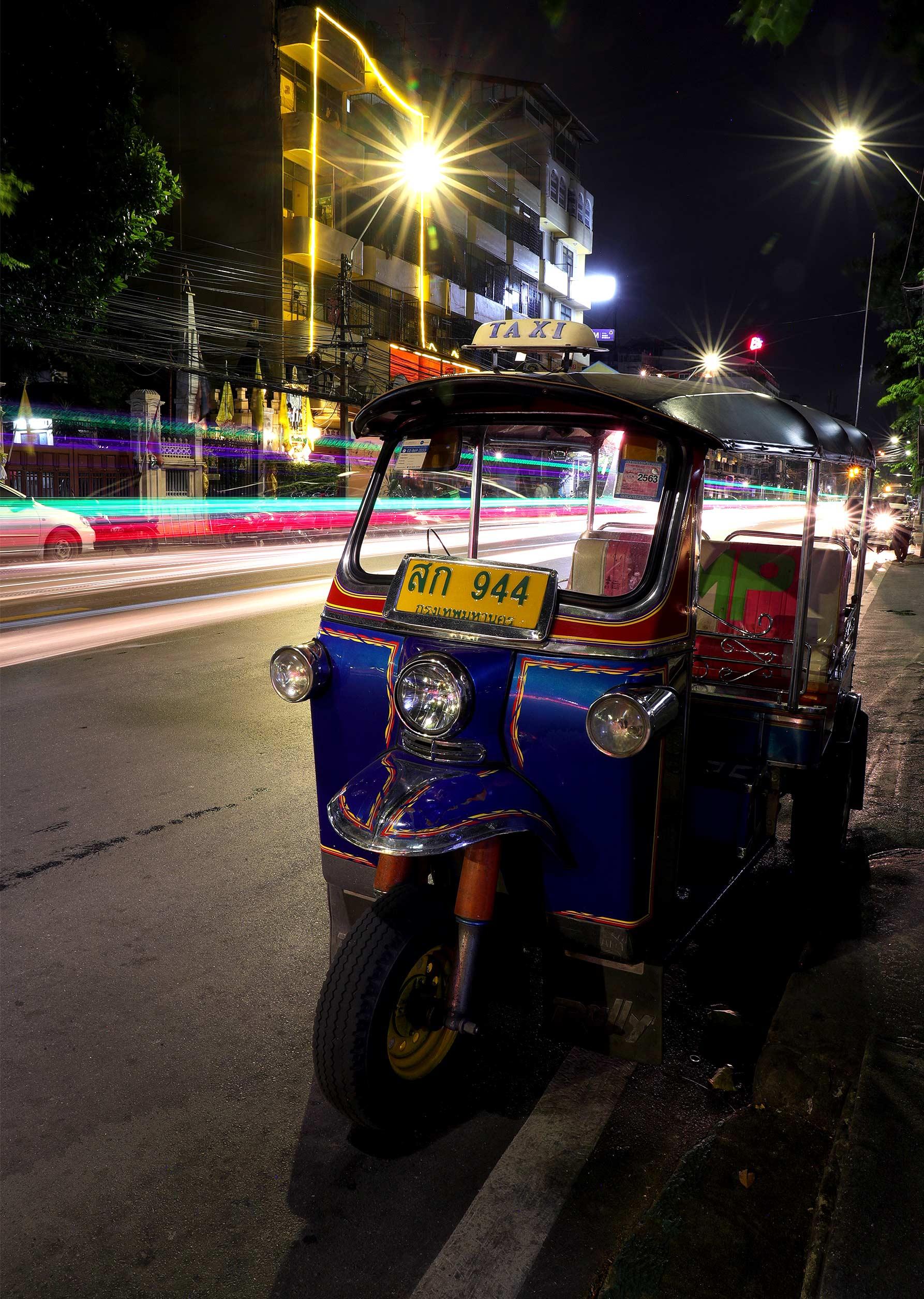 Long exposure night time photograph of a tuk tuk in Bangkok.