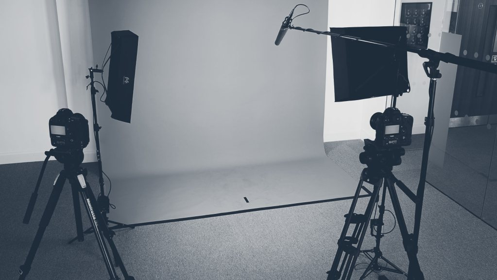 Photograph of a filming studio with lights, cameras and backdrop.