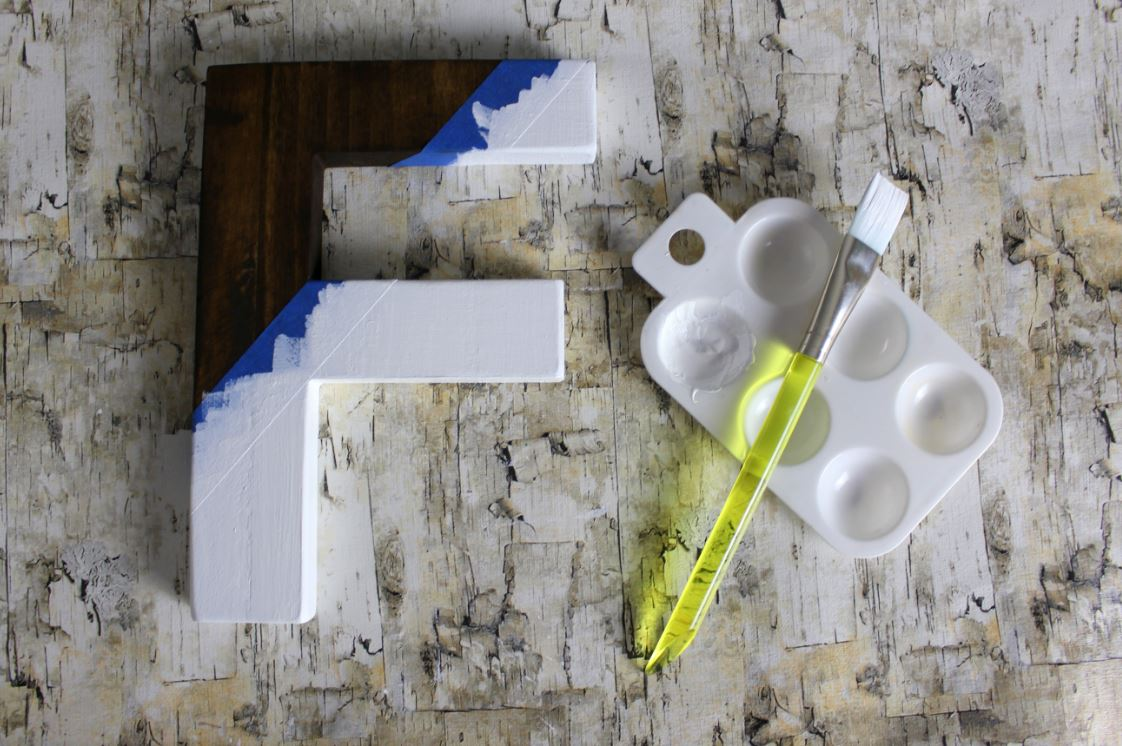 Applying paint to make your own color block letter.