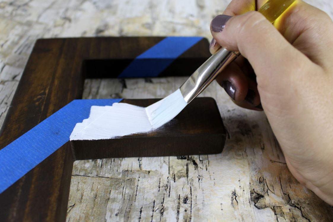 Paint away from the painter's tape when applying paint to the wooden letter.