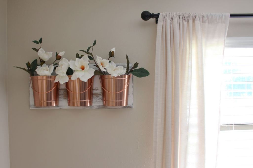 Create a wall hanging using a piece of wood and copper buckets.