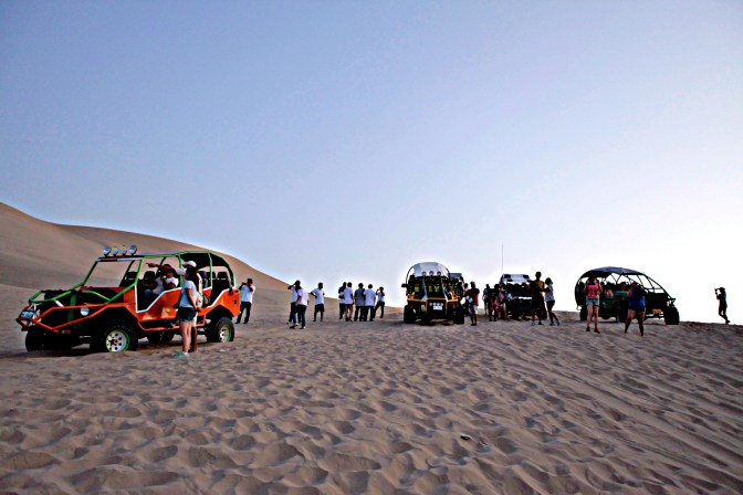 The dune buggies line up in the sand.