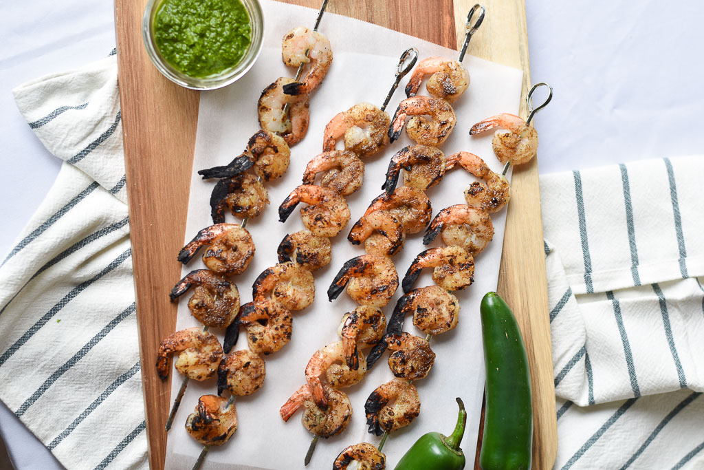 Four Grilled Shrimp Skewers with Jalapeno Chimichurri in a jar.