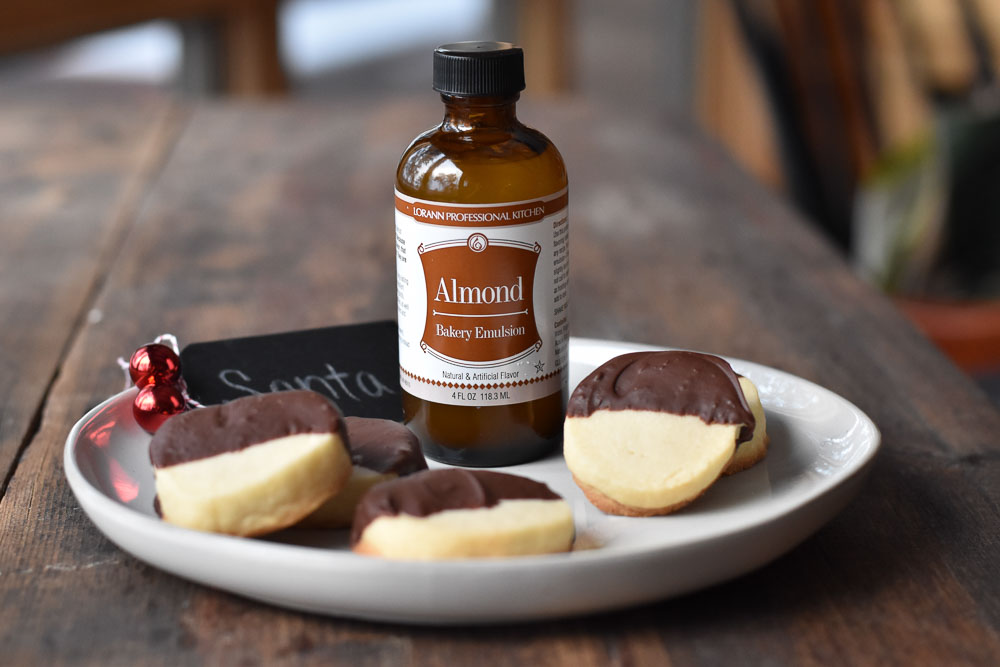Dark Chocolate Dipped Almond Shortbread Cookies with a bottle of LorAnn almond bakery emulsion
