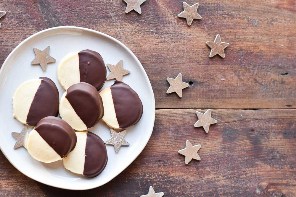 Dark Chocolate Dipped Almond Shortbread Cookies on a plate with stars