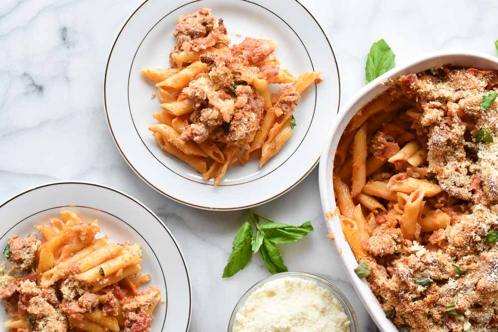 Two plates and a casserole dish of creamy sausage pasta bake