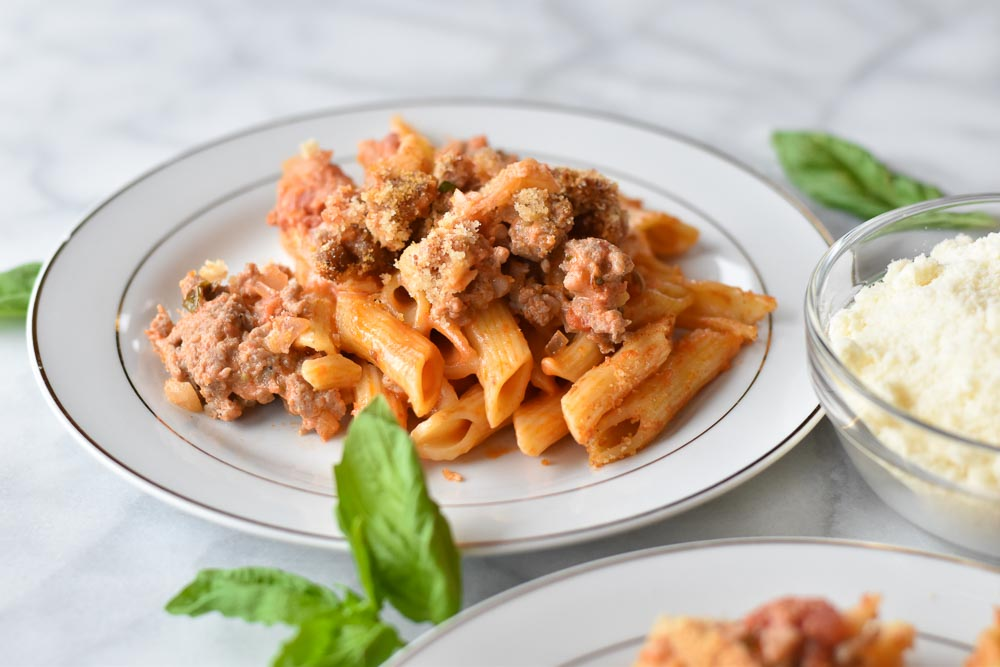 Side view of a plate of creamy sausage pasta bake