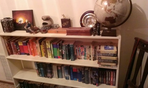 A bookcase with the books arranged by colour