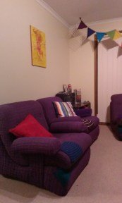 The left half of a lounge room with bright furniture and decorations