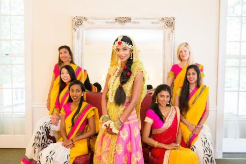 THE ONE AT THE MEHENDI where we do indian matching bridesmaids outfits witty vows | Indian bride with her bridesmaids in matching out fits yellow and pink stress | flower jewellery