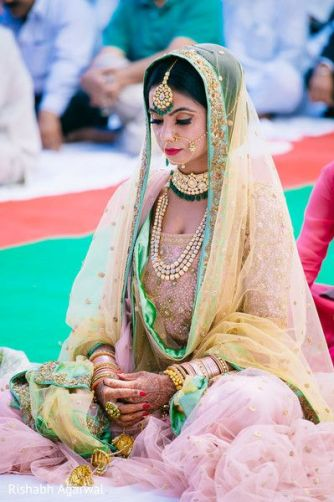 Pink net bridal lehenga with gold sprinkles paired with a yellow net dupatta and green detailing for the day wedding | Photo Rishabh Agarwal | Curated by Witty Vows