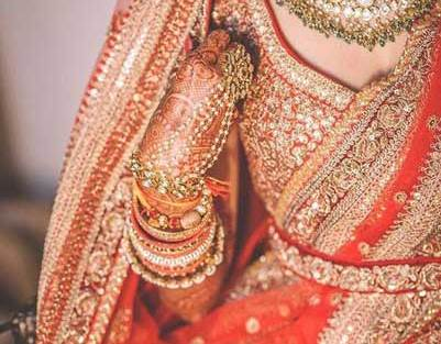 Orange hued Sabyasachi lehenga with traditional gold detailing and hand work | Photo by Cupcake productions | Curated by Witty Vows