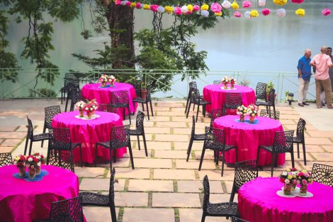 Pink Mehendi round table linen decor with mason jars and colourful flowers with cut lemon and orange slices under the paper pom poms   Jonathan & Subhashree   Curated by Witty Vows