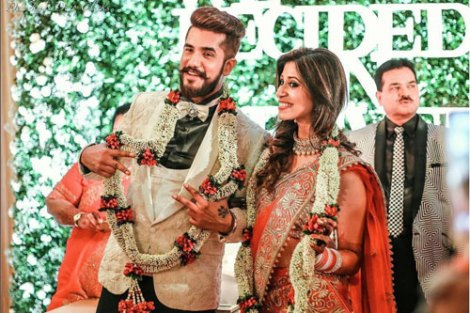 Indian Wedding Ideas from Suyyash and Kishwer's Wedding Reception   Kishwer in red lehenga with a gold blouse and detailing in mirror & Suyyash in a white tux   we decide on forever backdrop with letters white on green grass backdrop   Candid couple photo shoot ideas