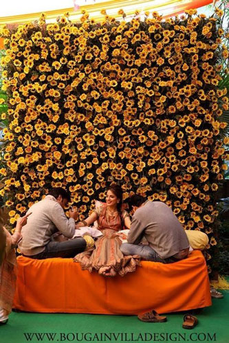 innovative mehndi decor ideas | beautiful mehndi Bridal seat sofa for bride with a flower studding backdrop in yellow and green contrasting the orange sofa lounger | Decor by Bougainvilla design