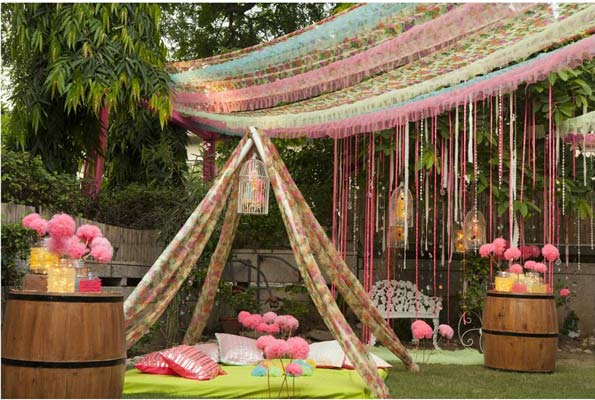 innovative mehndi decor ideas | Kitschy and creative pink and lime green neon mehendi decor with camp style canopy with gaddi and floor cushions of rtes bridal seat | chintz floral prints | Decor by - Rani Pink Decor