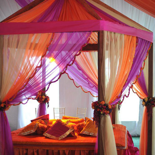 innovative mehndi decor ideas | pink orange and creme canopy with flower curtain ties and bridal bed seating for the mehendi