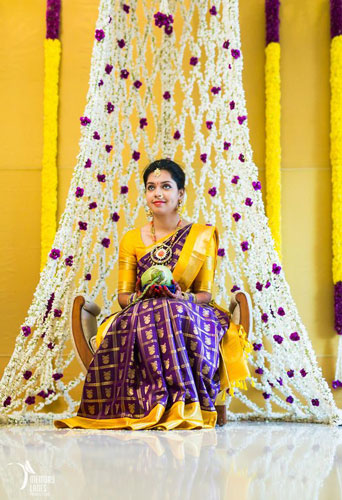 innovative mehndi decor ideas | Bridal seat chaise with a floral curtain in white Rajni flowers | South Indian wedding | Bride in kanjivaram silk saree yellow and purple colour | Photo by - Memory Lanes