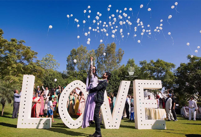 Love alphabets with balloons in white with Indian couple posing | couple photoshoot ideas | Indian bride in pretty pink gown | Indian wedding photo booth ideas | Photo Op ideas | fun wedding photos | Cupcake Production