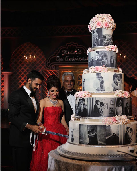 personalised wedding cakes | Indian Wedding Cakes | Bride and groom cutting cake Indain wedding | Reception cake with Indian couple's black and white photos on tiered cake with pink gum paste flowers | source- axioo