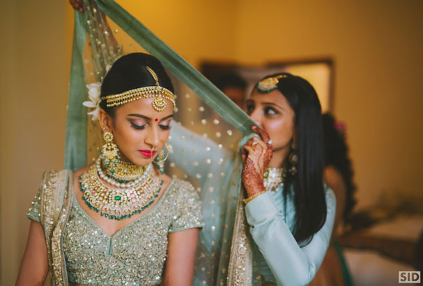 Top Indian Bridal Makeup trends | Makeup for bride | Getting ready photo | wedding look - Kundan and emerald bridal jewellery | pretty Indian bride with in mint green lehengas with a bright red lipstick | Makeup idea | Photo by - Total Siddharth Photography