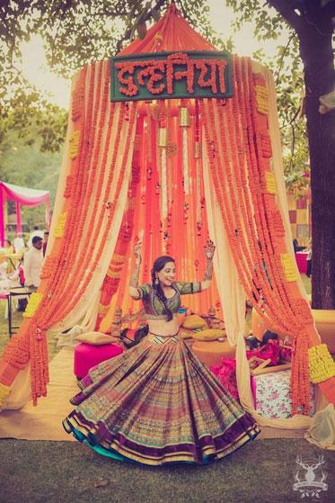 Indian bride twirling outside her mehendi bridal bed | innovative mehndi decor ideas | Marigold decor | Photo by Morvi Images | Bridal Seat Ideas
