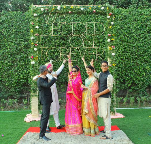 Indian bride with family with DIY photo op made with metal letters we decided on forever| Green and floral truss | Indian wedding photoshoot ideas | Indian bride in pretty pink gown | Indian wedding photo booth ideas | Photo Op ideas | fun wedding photos | Photo Buddies