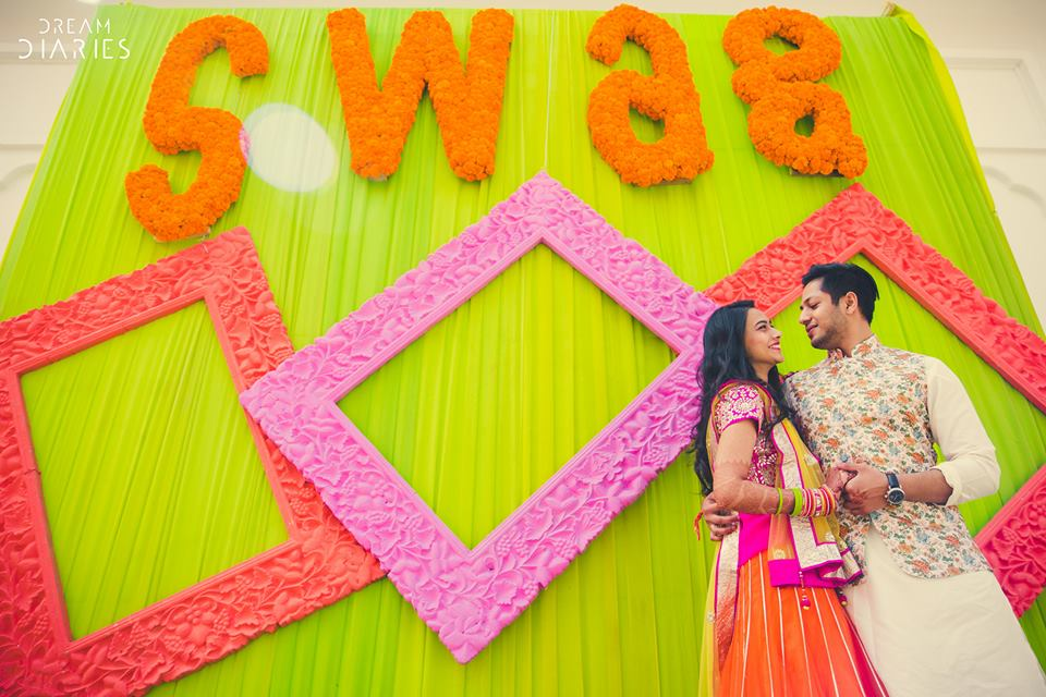 pink and peach Colourful photo frames with marigold letters swag on a lime green wall | Indian wedding photo booth ideas | Photo Op ideas | fun wedding photos | Dream Diaries
