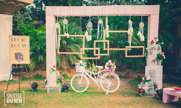 photo op A rustic backdrop with cages flowers and photo frames with a pretty decorated white bicycle | Indian wedding photoshoot ideas | Indian bride in pretty pink gown | Indian wedding photo booth ideas | Photo Op ideas | fun wedding photos | Shutter down
