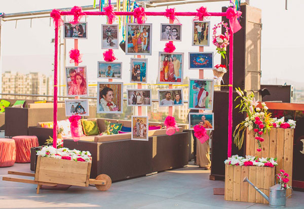 photo op backdrop with family photos hanging and polaroids with pink paper and fabric flowers | Indian wedding photoshoot ideas | Indian bride in pretty pink gown | Indian wedding photo booth ideas | Photo Op ideas | fun wedding photos