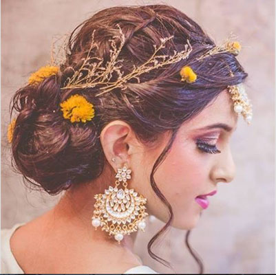Pretty bride with boho bun hair style with a fresh flowers | Hairstyle with flowers | fresh flower hairstyle - orange flower buds flowers in your hair | Mehndi hairstyle