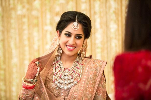 Ridhi Mehra wedding | Indian bride wearing pretty polka and peal necklace, haathphool and maangtika with a pale pink sabyascahi lehenga