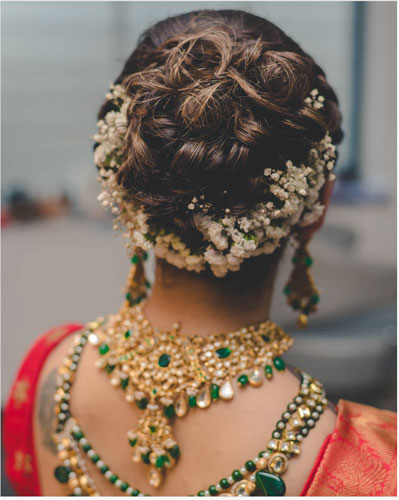 A pretty bun with curls and flowers on the underside | Indian wedding hair style bun with flowers | babusbreath