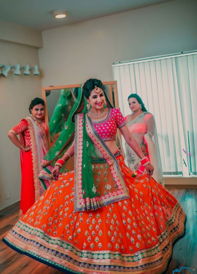 must have wedding pics for your wedding album | the bridal twirl photos | Indian bride in an orange and gold lehenga with pink blouse and green dupatta
