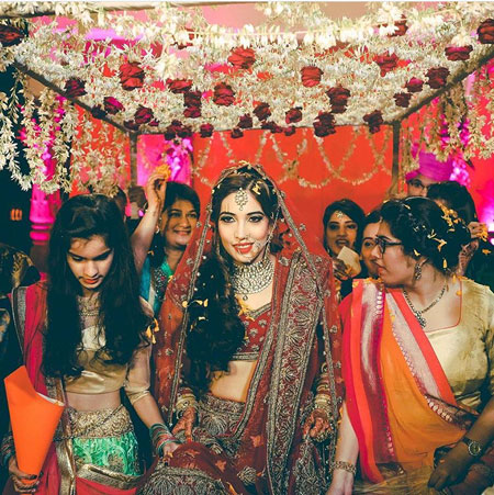 Indian bridesmaids duties   Bride's friends   BFF photos from Indian wedding   Indian bride and her friends under the floral hangings phoolon ki chadar
