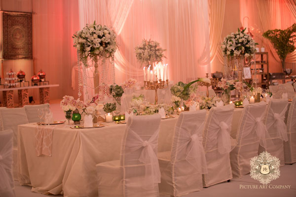 Ridhi Mehra's wedding photos | reception decor in ivory and gold with bow tied chair backs