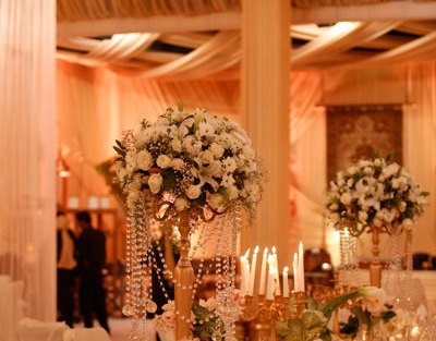white rose and lily centrepieces with gold candle bras and crystals | Ridhi Mehra wedding