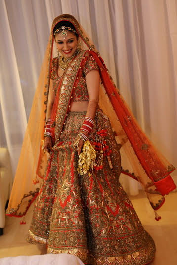 Indian wedding ideas | Indian bride wearing a carrot red lehenga with gold dab work all over | Orange dupattas | Kundan Jewellery - Navratan matahpatti and chura