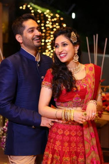 Groom in a blue bandhgala suit and bride in a pretty embroidered red lehenga and a Kundan jhoomar