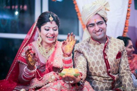 plush affairs photography | Jabalpur wedding | high school sweethearts | Divya and Nikhil | groom in a beige and cream sherwani with gold motifs and bride in a red and gold lehengas | Indian bride and groom jaimala happy