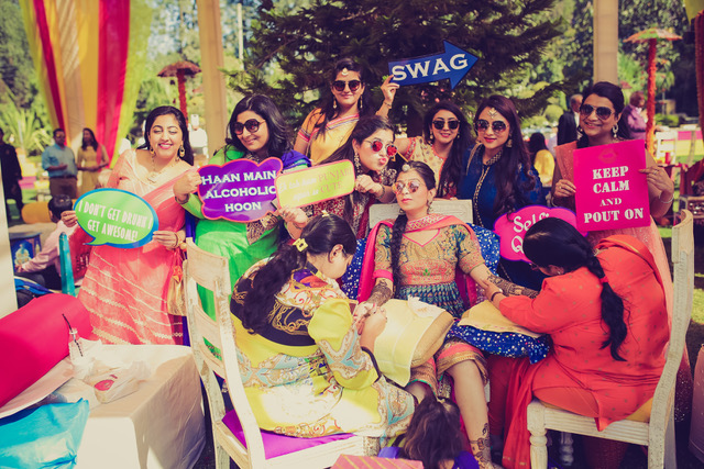 Indian bride with her colourful bridesmaids at her mehndi holding photo booth signs   Purva and Sahil wedding   wedding in Delhi   Morvi Images