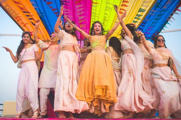 Masoom Minawala holi party | indian bride with bridesmaid | colourful Indian party tent | Indian bride Masoom minawala wearing yellow beige plain lehenga | happy Indian bride | Indian blogger's wedding | Indian wedding trends