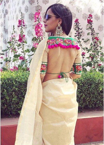 Latest blouse styles | new blouse styles to love | latest blouse designs for Indian brides | Indian bride with beautiful twisted braid with baby's breath flowers | Open back cut out style blouse with colourful pom poms sexy blouse styles