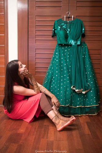 Dhruv and Saina   Delhi wedding   bride lovingly gazing at her green lehengas   getting ready shot you must have