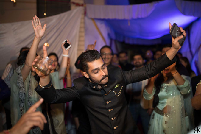 Indian groom dancing at this wedding with a glass of whiskey in his hand