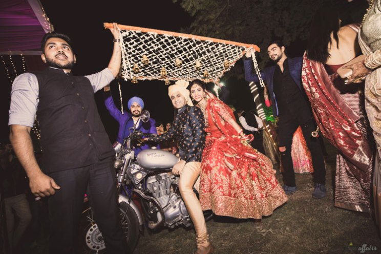 JyotPriya and Nishant | Punjabi wedding in Delhi | The bride's wedding entry on a Royal Enfield with her brother was so cool and quirky.