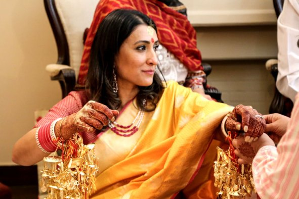 Samiksha and Tony | NRI couple | Lutyens Delhi wedding | The bride having a candid moment in a beautiful mustard yellow saree with her chura.