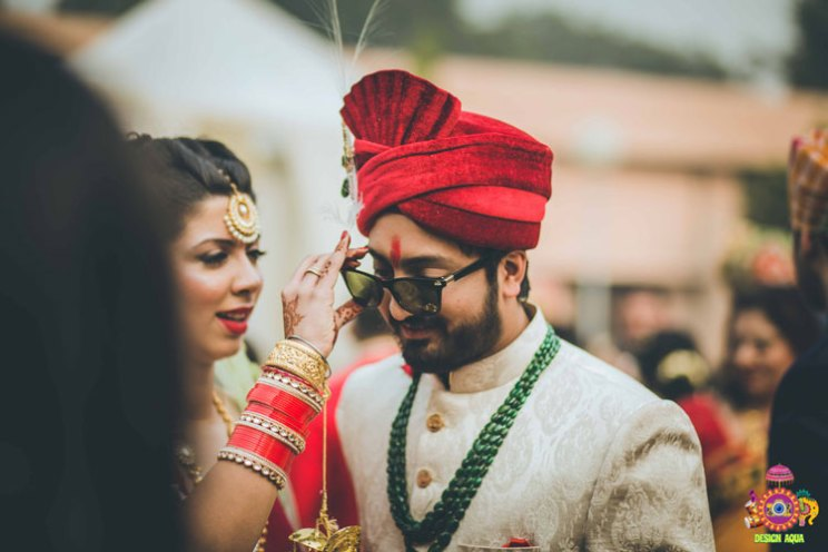Chitrakshi and Neil | Offbeat wedding in Delhi | Day wedding full of ideas | Indian bride wearing an ivory lehenga with a floral sleeve blouse and a red and pista pastel double dupatta | Indian bride with a red sweetheart blouse with red white and green 3d flower decoupage on the sleeves |  Indian bride and groom drinking beer together | photo by Design Aqua | WIttyVows | Bride stealing groom's sunglasses